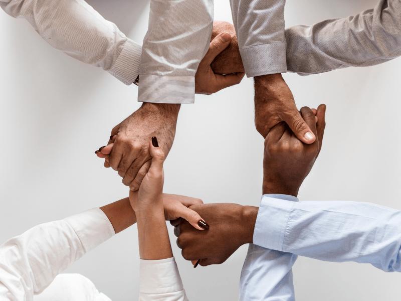 people holding hands representing teamwork